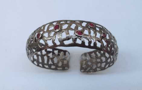 18 carat white gold bangle, black rhodium plated, rubies