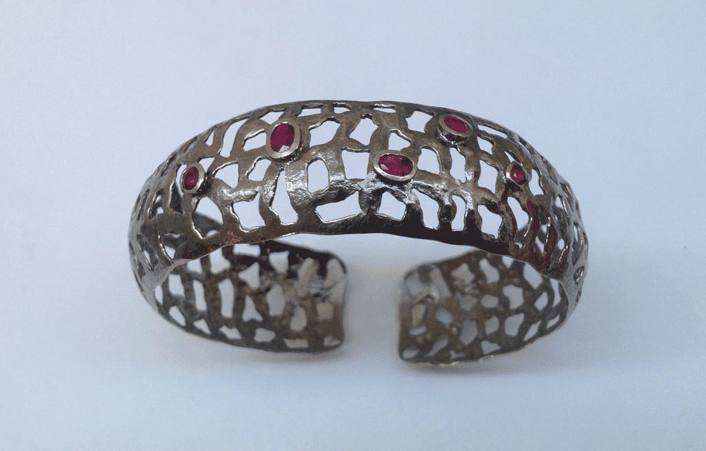 18 carat white gold bangle, black rhodium plated, rubies