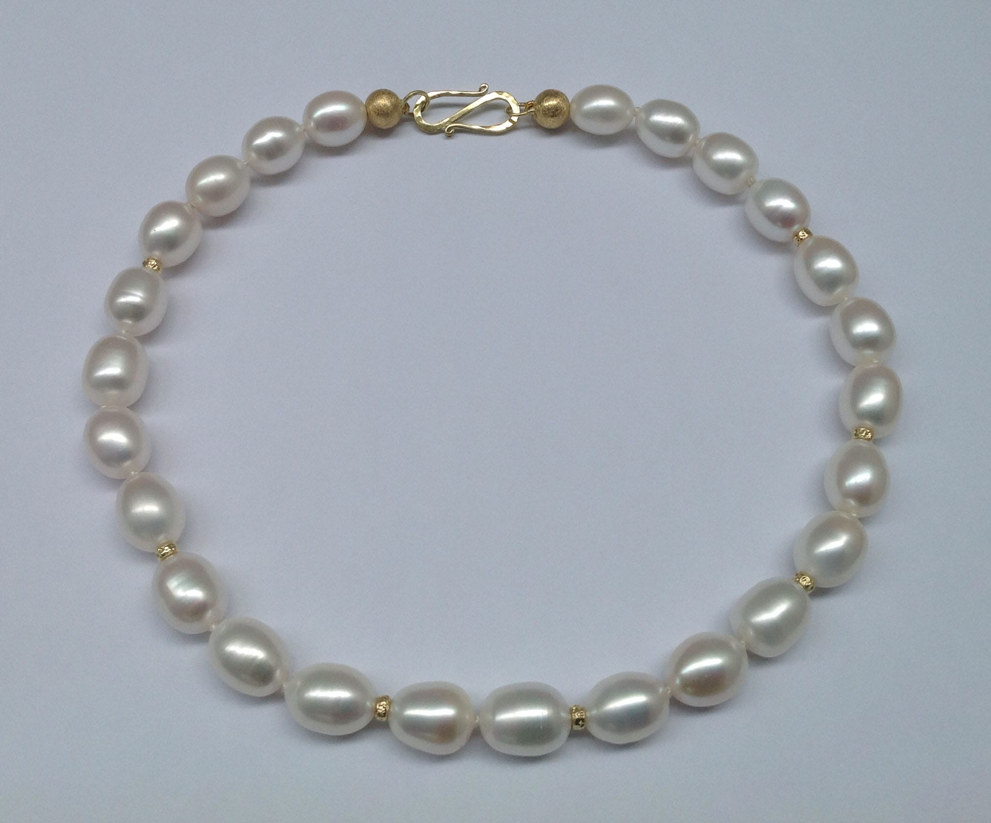 Oval white freshwater pearls, 18 carat yellow gold beads and clasp