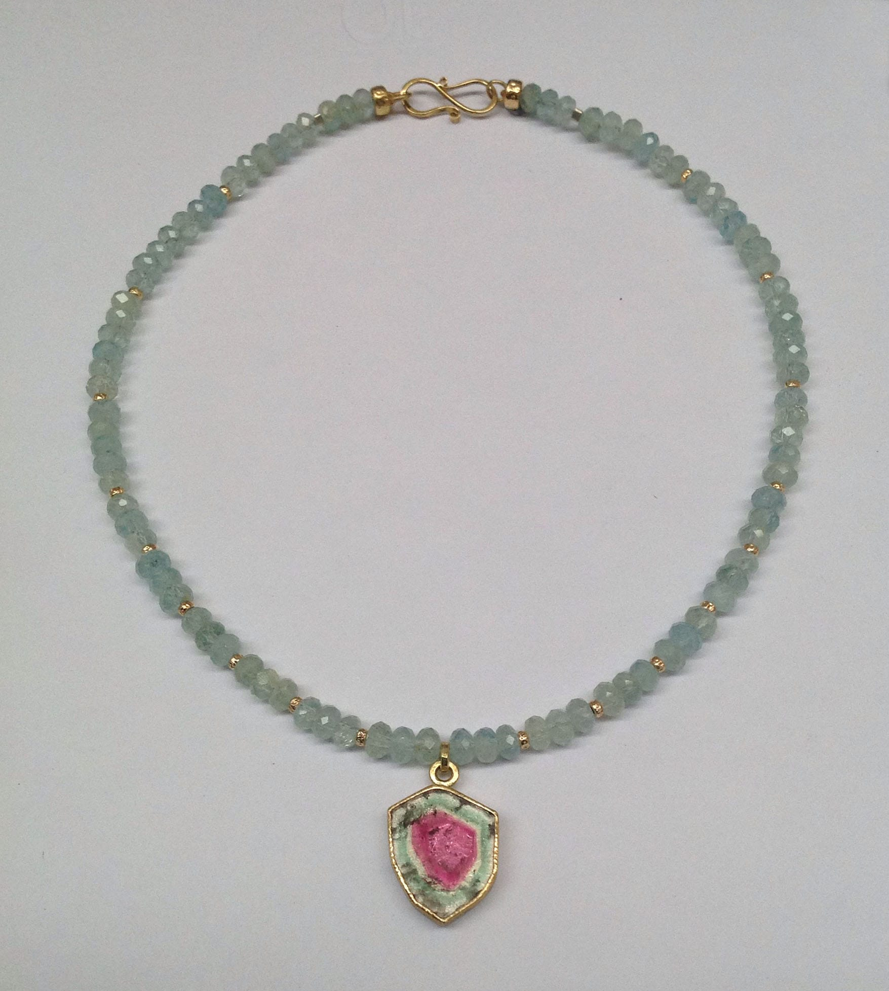 Watermelon tourmaline set in 18 carat yellow gold, faceted aquamarine beads