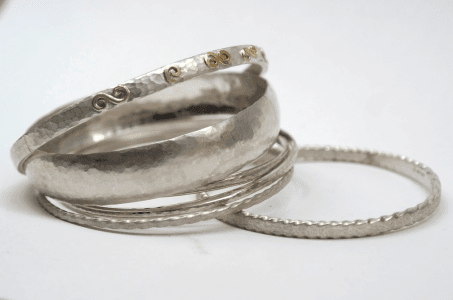 Collection of sterling silver bangles including with gold detail