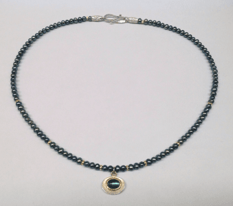 Indigolite set in 18 carat yellow gold, sterling silver, peacock pearls, 18 carat yellow gold beads