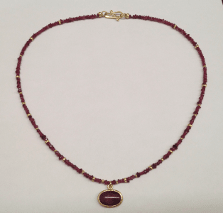 Opaque ruby set in 18 carat yellow gold, ruby, garnet and 18 carat yellow god beads