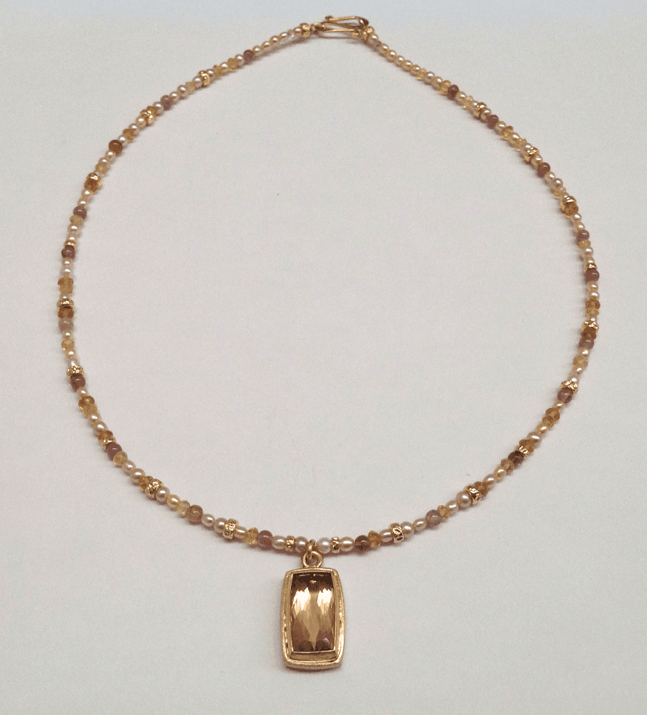 Faceted peach tourmaline set in 18 carat yellow gold, tourmaline beads and cream pearls