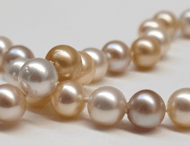 Detail of Pink freshwater pearls with white and golden South sea pearls, 10mm in diameter. 18 carat white gold clasp studded with 12 diamonds.