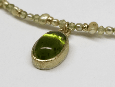 Detail of Peridot set in 18 carat yellow gold, peridot beads, freshwater pearls