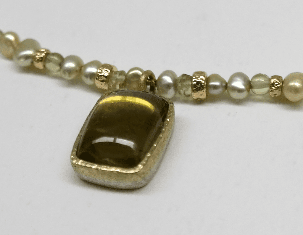 Detail of Yellow tourmaline set in 18 carat green gold, peridot beads, green pearls and 18 carat yellow gold beads