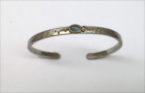 Sterling silver and 18 carat yellow gold bangle with aquamarine and blue diamond